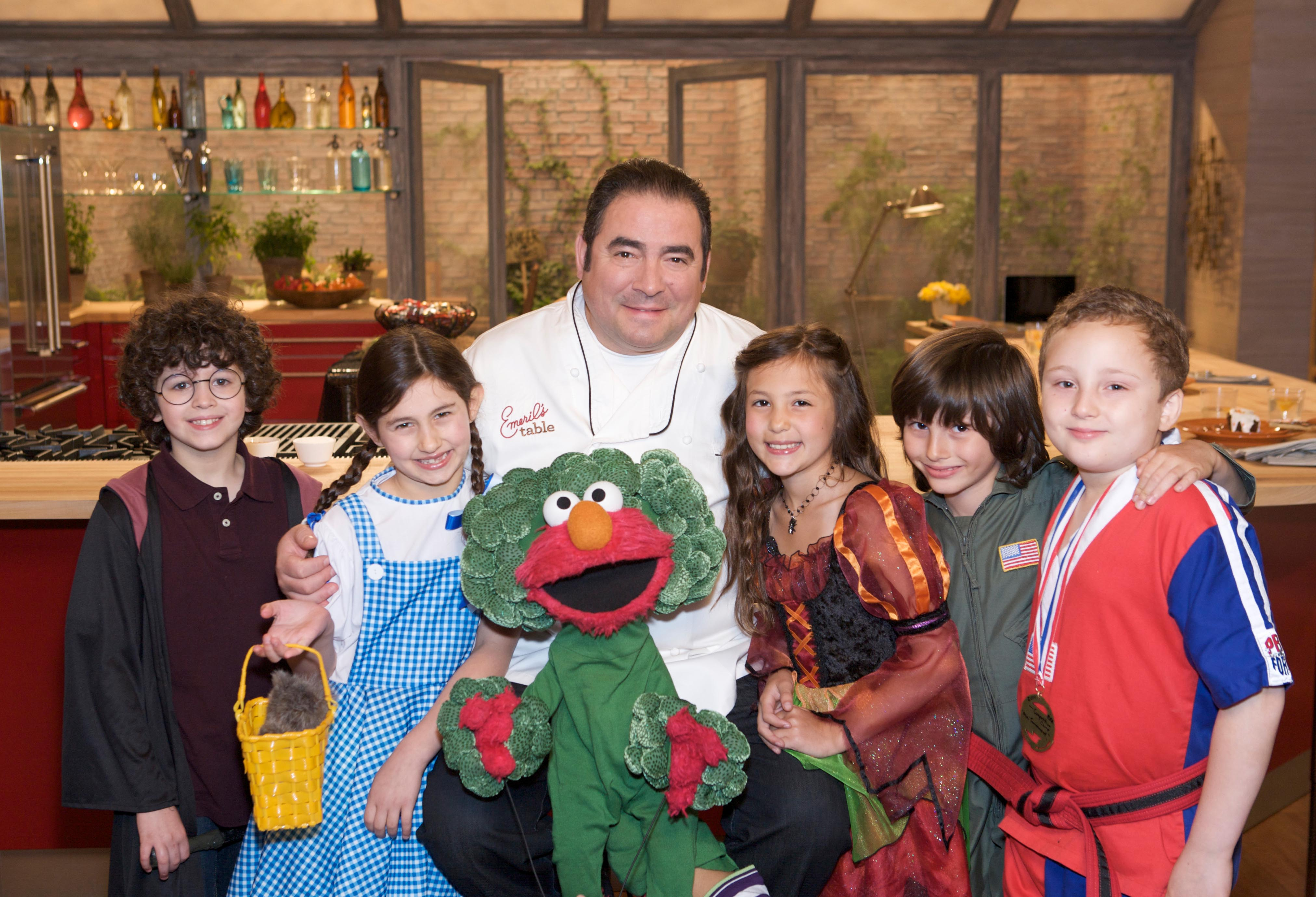 "In this photo from Hallmark Channel's ""Emeril's Table"" Chef Emeril Lagasse welcomed trick-or-treaters Joseph Kennedy, Molly Bochner, Sesame Street's very own Elmo (dressed as some nutritious broccoli!) , Olivia Debald, Jackson Fiero and Bjorn Bowser in this Halloween-themed episode."