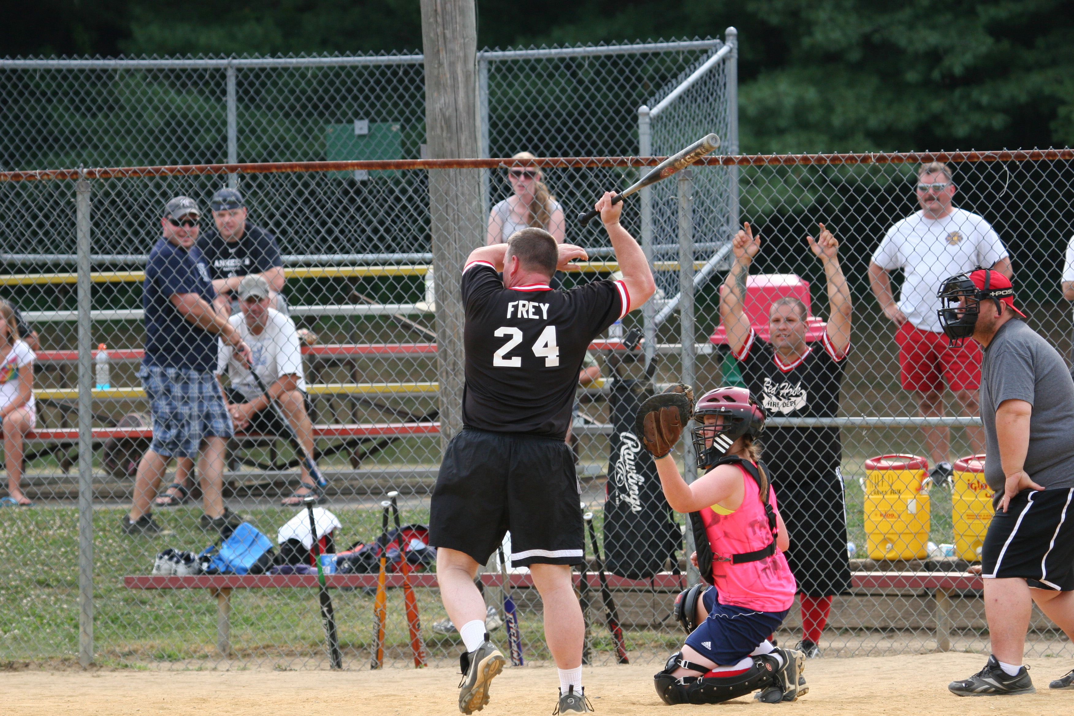 Fireman Rob Frey reacts to an inside fastball from high school all-star pitcher Elizabeth Brisley. The uniformed services were facing fast-pitch softball for the first time.