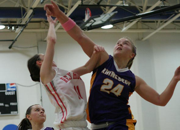 Rhinebeck's Rachel Tigges (#24) and Red Hook's Julianne Wilkinson (#11) take to the air under the basket to secure a loose rebound.