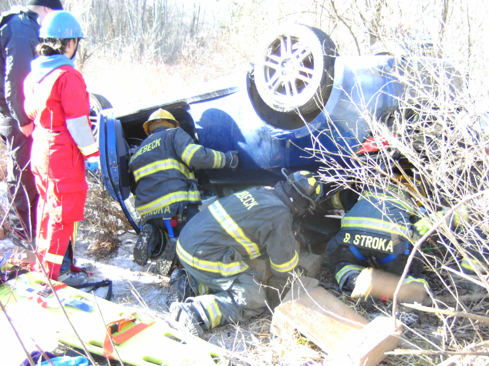 Emergency personnel work to free Nicole Arruda from her vehicle after it overturned off Slate Quarry Road.