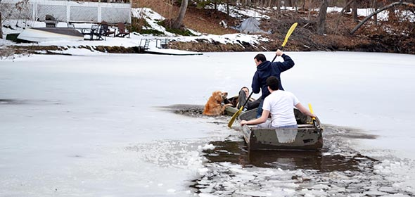 Chad (white shirt) and Brandon Cole (standing) maneuver a rowboat closer to Dana Tompkins and his dog Sampson during the icy rescue on March 10.