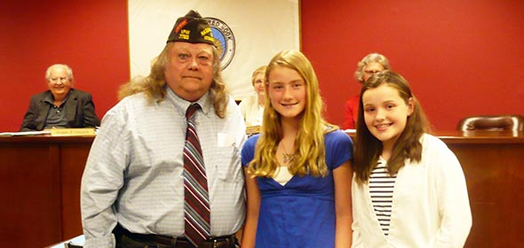Commander William Moore of the VFW with scholarship winners Hanlon Crane and Helena Crane.