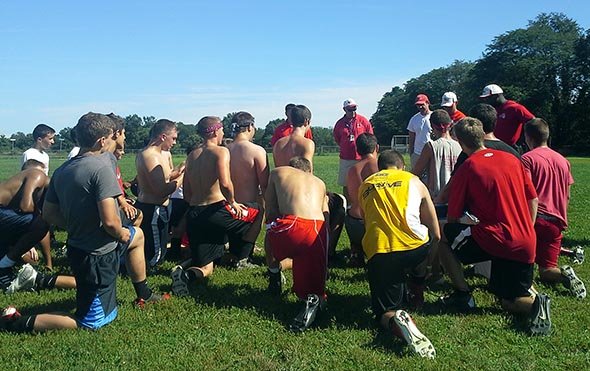 Red Hook football players take a knee for the coaching staff during August skills camp.
