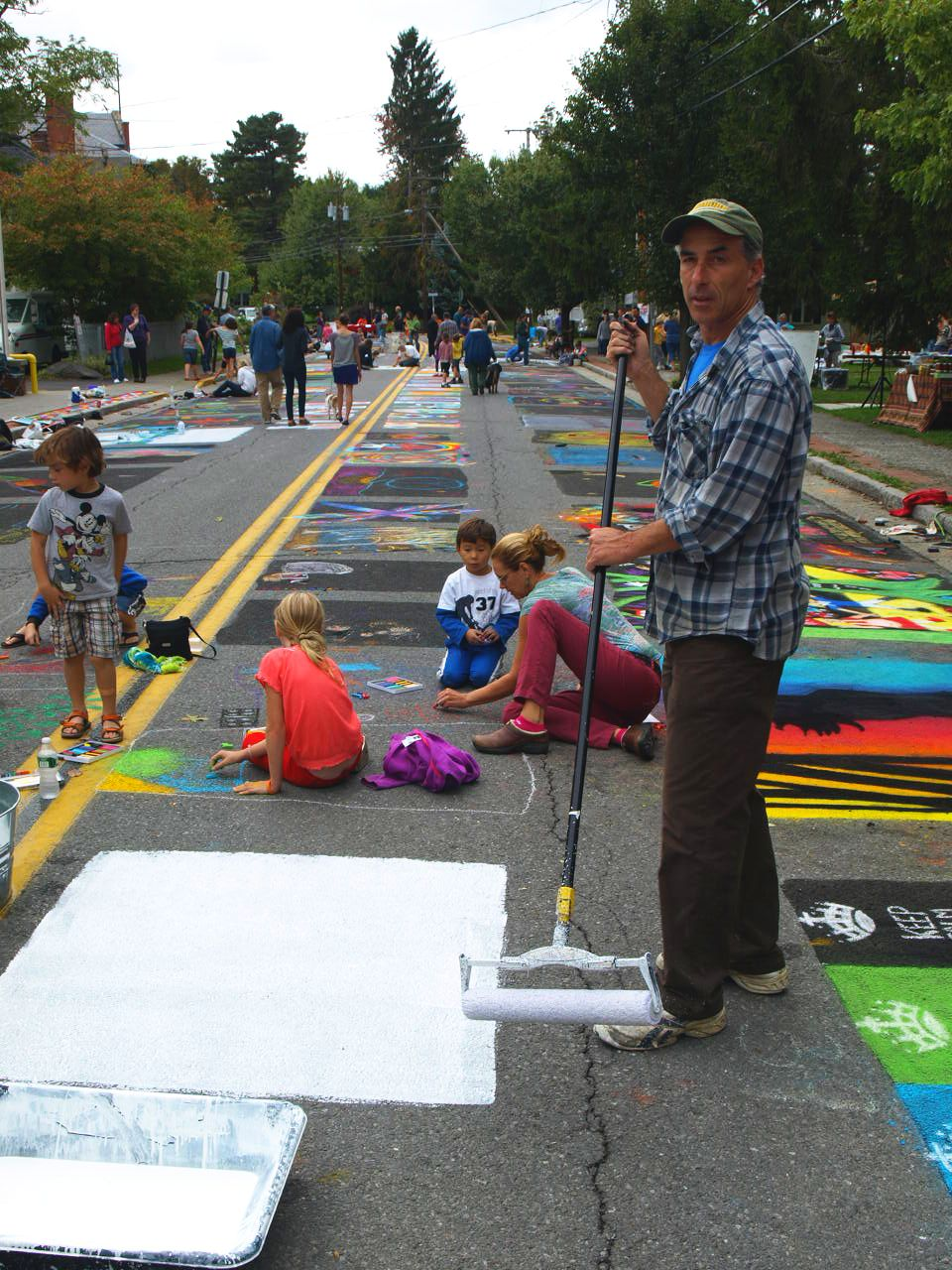 Robert McKeon paints white spaces for artists at the 2012 Tivoli Street Painting Festival.