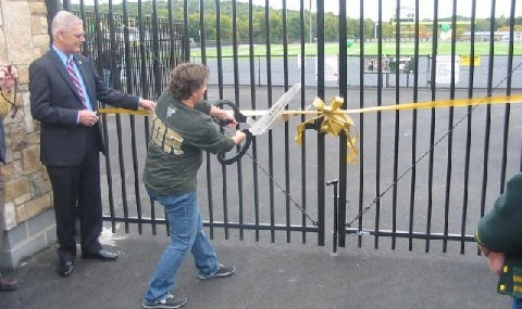 Big Scissors, Big Moment:  With guidance from Board of Education President Doug Hieter, Director of Physical Education, Health and Athletics, Amy McArdle-Rausenberger cuts the ribbon on the gates of the new sports complex at FDR High School.
