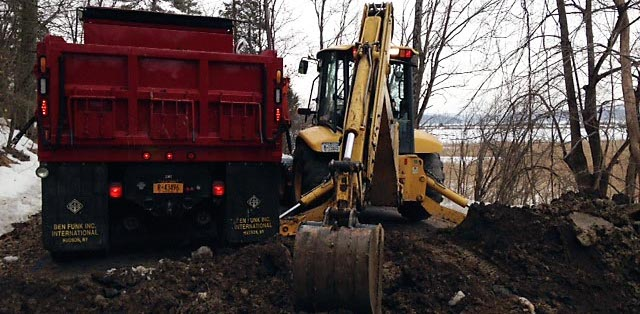 Rhinebeck Highway Dept. Foreman Bob Wyan operates the backhoe as crew works to repair sinkhole on Mill Road March 11.  Courtesy Photo / Rhinebeck Highway Department